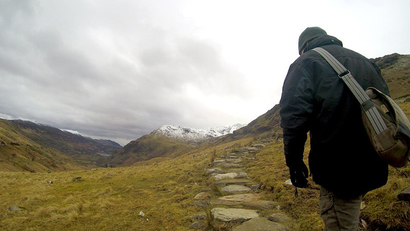 Man from back Climbing Snowdon in Wales in Winter via the Pyg Track