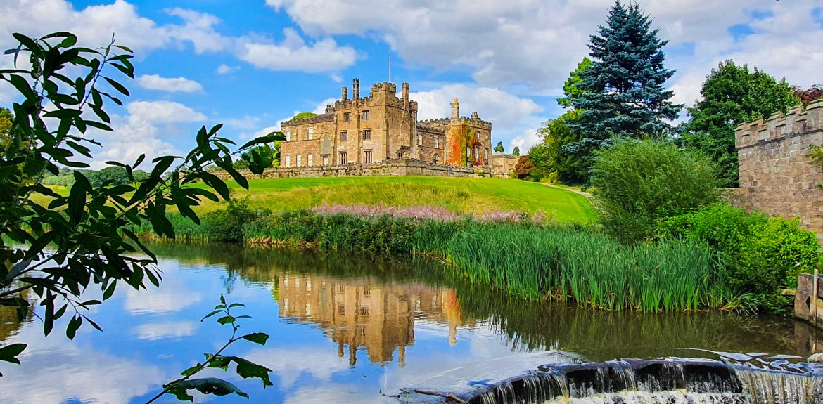 View of Ripley Castle from across the pond with a waterfall in the foreground