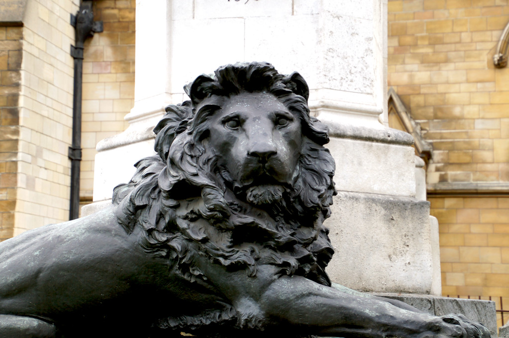 lion statue in front of london parliament building