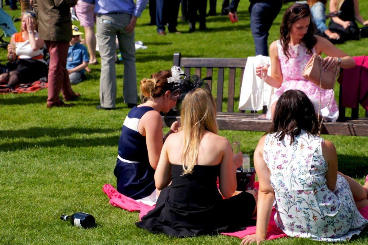 Women in fancy outfits at the Newbury Racecourse main field on al shaquab lockinge day