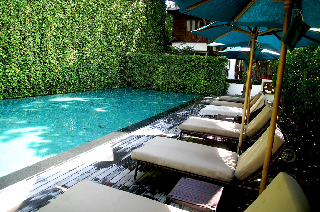 lounge chairs beside pool of 137 pillars house in chiang mai thailand